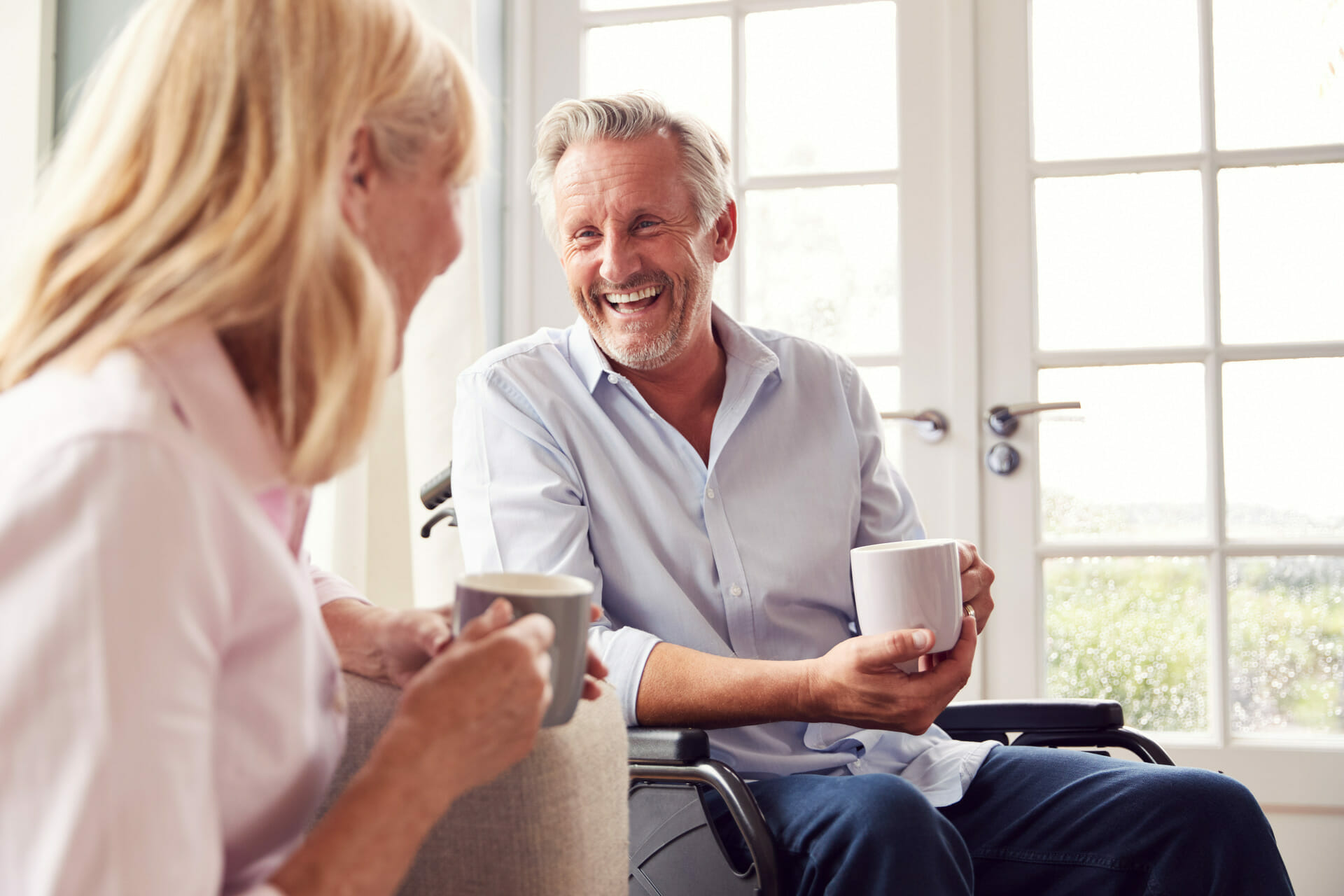 a happy older couple discussing viatical settlements over coffee