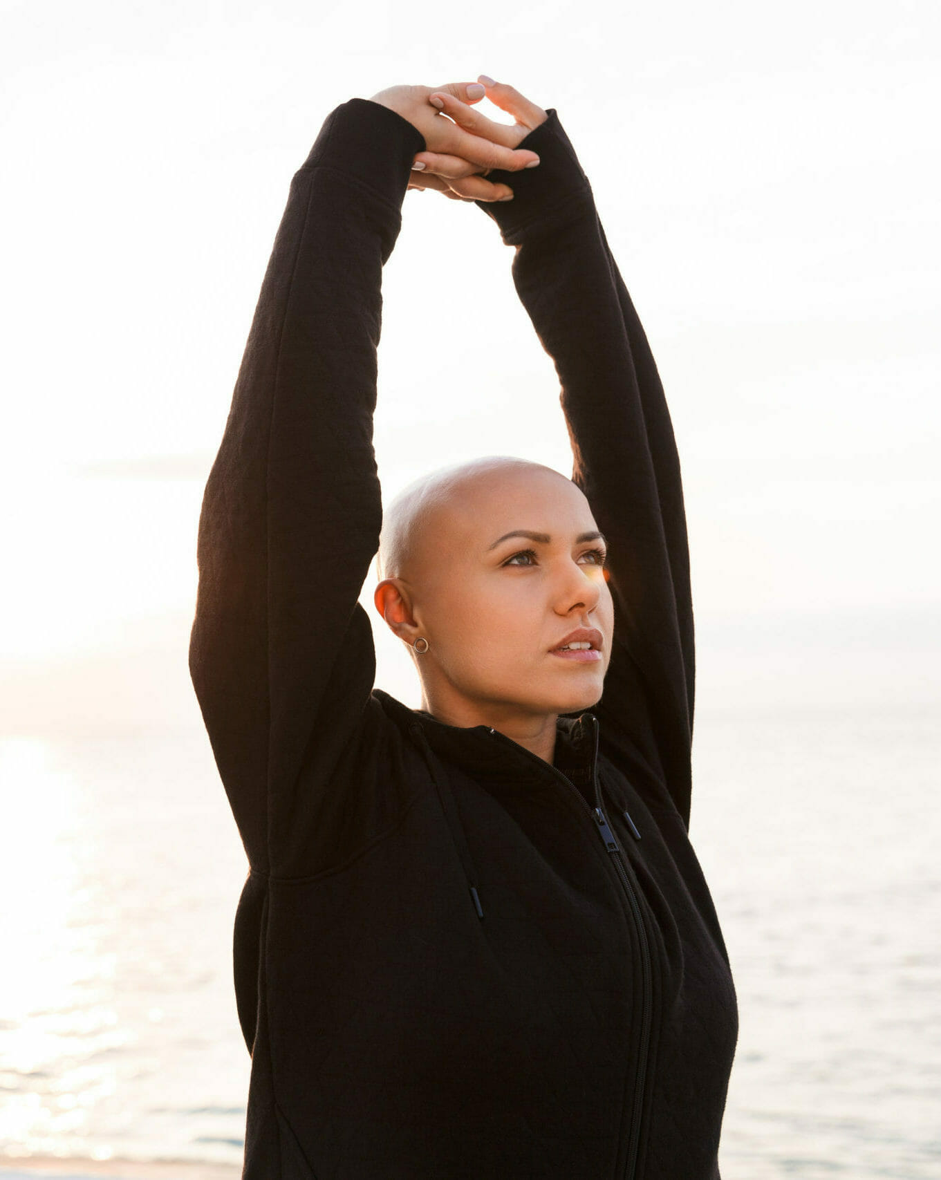 organizations that help cancer patients financially bald cancer patient doing yoga on the beach